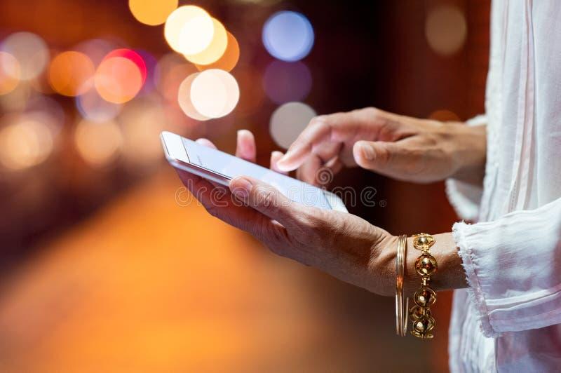 Mani della donna facendo uso dello smartphone alla notte fotografia stock