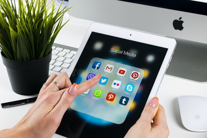 Mani della donna facendo uso di iPad pro con le icone del facebook sociale di media, instagram, cinguettio, applicazione di Googl fotografie stock libere da diritti