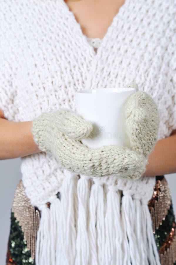 Mani della donna in guanti che tengono tazza immagine stock