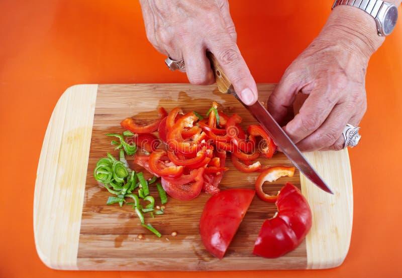 Mani della donna maggiore che tagliano le verdure fotografia stock