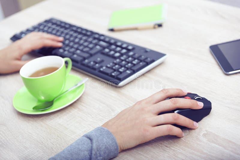 Mani della donna su una tastiera immagini stock