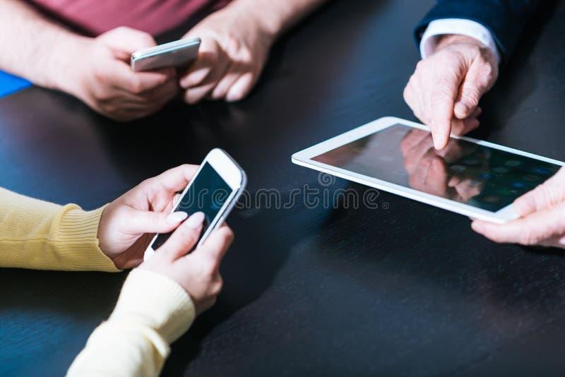 Mani della gente facendo uso dei telefoni cellulari e della compressa digitale immagine stock libera da diritti
