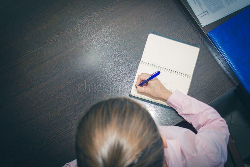 Mani della giovane donna che tengono le pagine aperte del taccuino su una tavola scura, vista superiore la lista il medico scrive fotografie stock