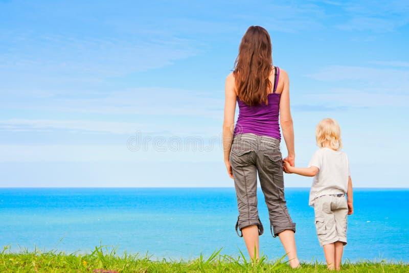 Mani della holding del bambino e della madre dall'oceano fotografie stock libere da diritti
