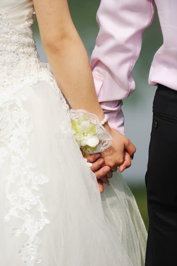 Mani della holding dello sposo e della sposa fotografia stock