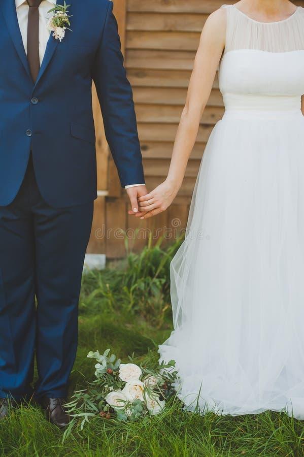 Mani della holding dello sposo e della sposa immagini stock libere da diritti