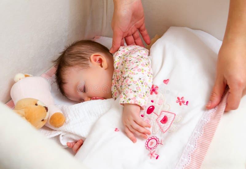 Mani della madre che accarezzano il suo sonno della neonata immagine stock libera da diritti