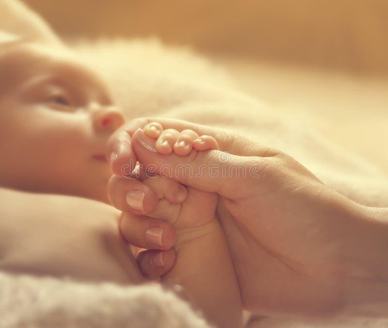 Mani della madre della tenuta del bambino, salute neonata malata, aiuto neonato fotografia stock libera da diritti