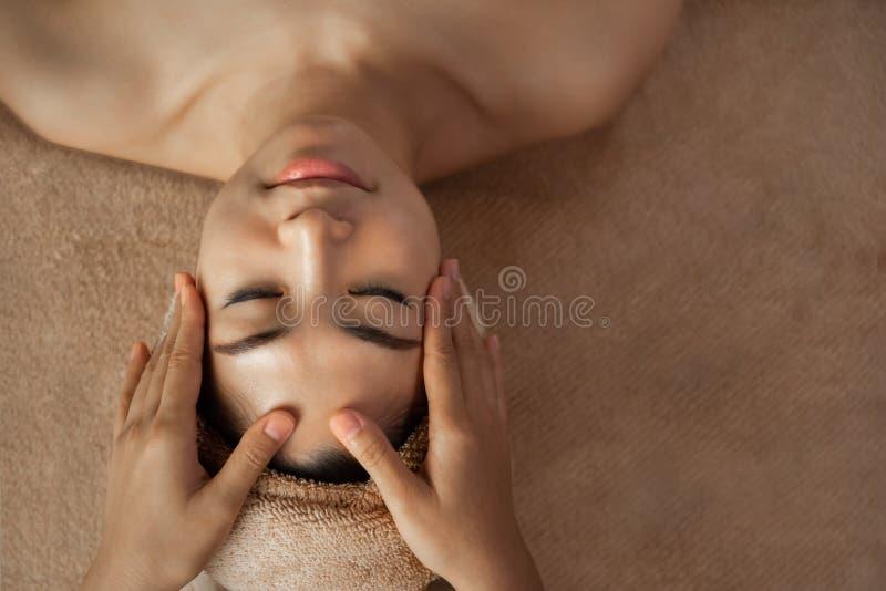 Mani della massaggiatrice che fanno massaggio di fronte fotografia stock libera da diritti