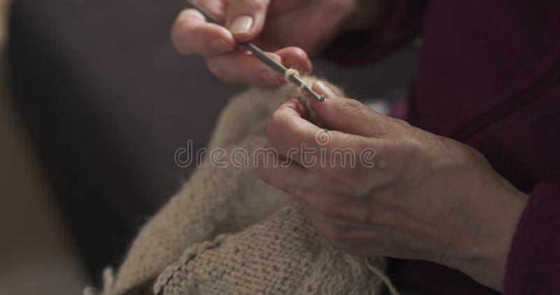 Mani della nonna del primo piano che tricottano maglione fotografia stock