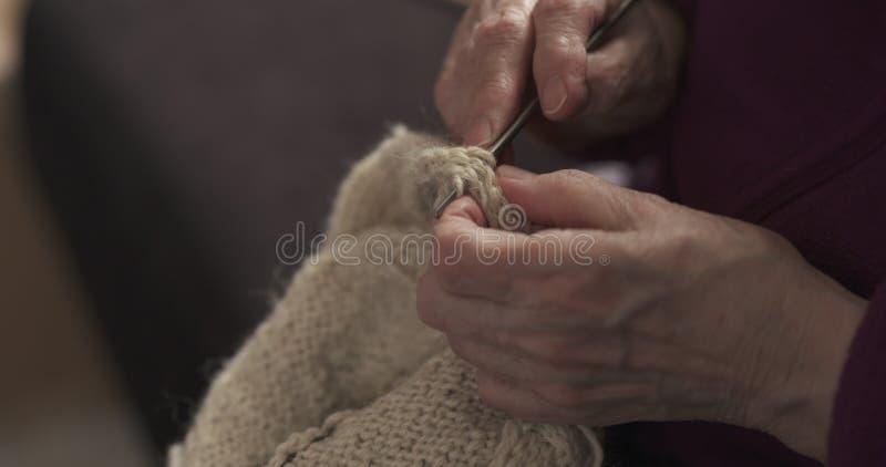 Mani della nonna del primo piano che tricottano maglione immagine stock libera da diritti
