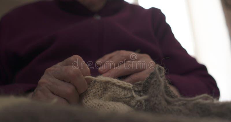 Mani della nonna del primo piano che tricottano maglione fotografie stock libere da diritti