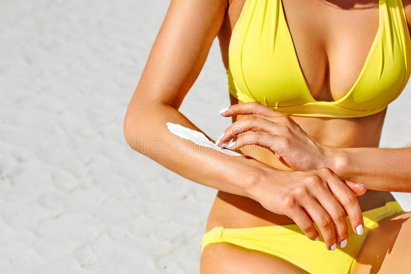 Mani della ragazza che applicano sunblock mentre sedendosi su una spiaggia di estate Cura di pelle Cosmetici Crema di Sun fotografia stock libera da diritti