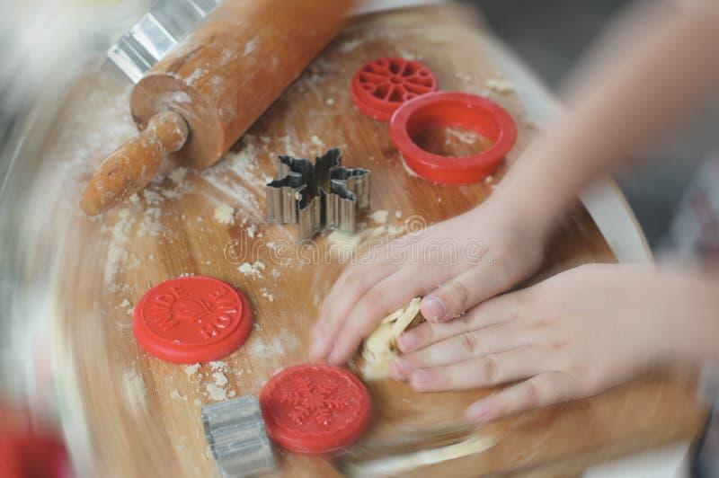 Mani della ragazza che impastano pasta per i biscotti di Natale fotografia stock