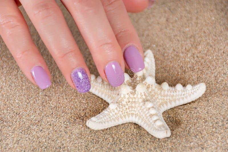 Mani della ragazza con le stelle marine e una sabbia di mare lilla di tocco del manicure di colore nei precedenti fotografia stock libera da diritti