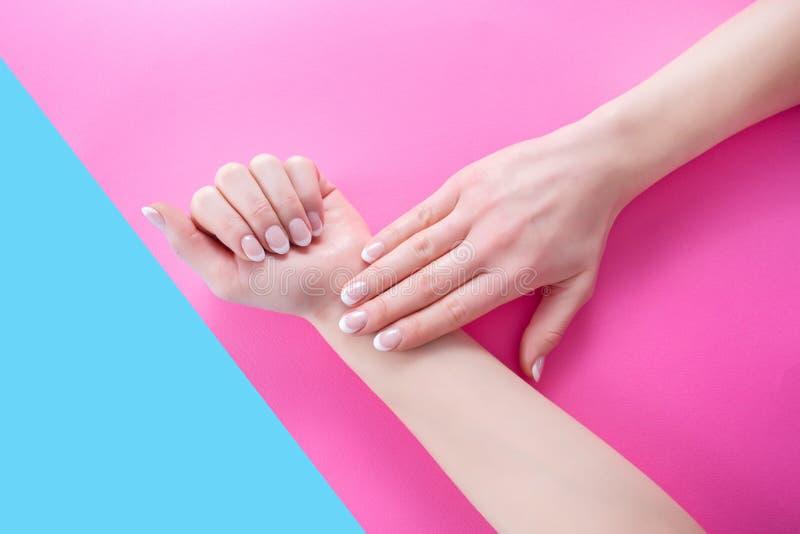 Mani della ragazza con stile francese del manicure delle unghie sul rosa e sul fondo pastello blu fotografia stock