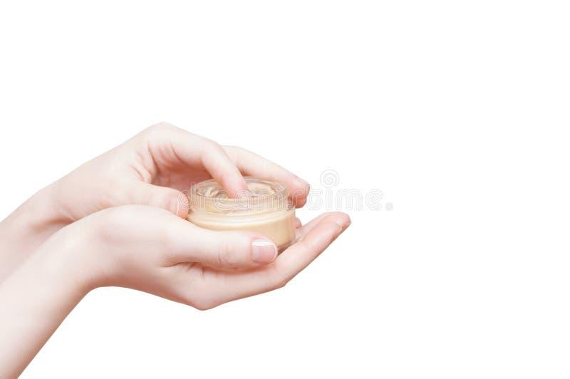 Mani della ragazza con un barattolo della fine della crema di fronte su isolato bianco immagine stock libera da diritti
