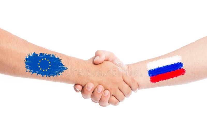 Mani della Russia e dell'Unione Europea che stringono con le bandiere fotografia stock libera da diritti