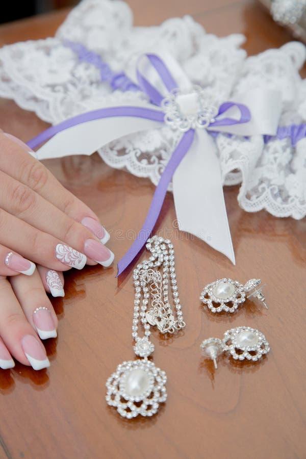 Mani della sposa con le decorazioni di nozze e di un bello manicure fotografia stock