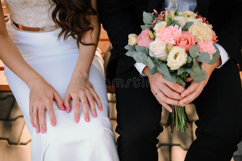 Mani della sposa e dello sposo con il mazzo di cerimonia nuziale fotografie stock libere da diritti