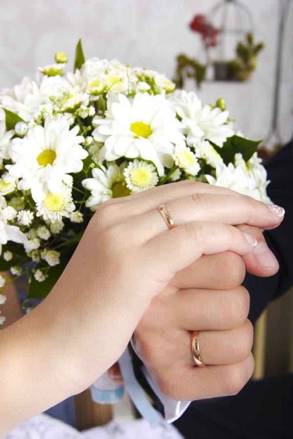 Mani della sposa e dello sposo con le fedi nuziali su un mazzo fotografia stock libera da diritti