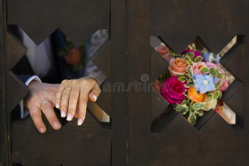 Mani della sposa e dello sposo con le fedi nuziali in una finestra di legno carven fotografia stock
