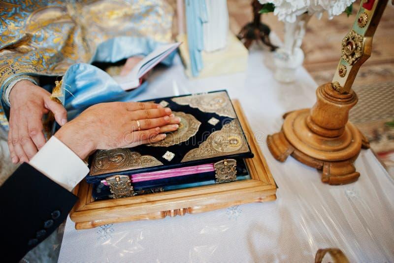 Mani delle coppie di nozze sul vangelo al giuramento immagine stock