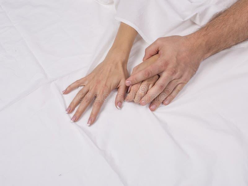 Mani delle coppie facendo sesso che tirano gli strati bianchi nel desiderio e nell'orgasmo immagini stock