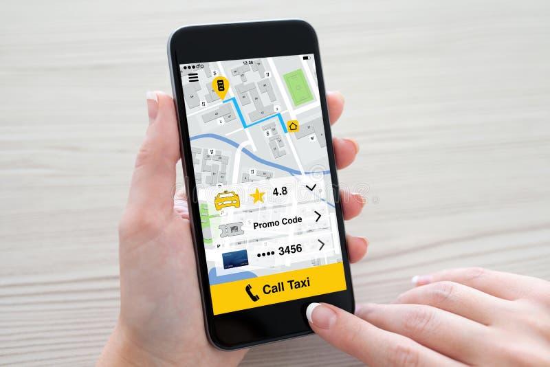 Mani delle donne che tengono telefono con il taxi di chiamata di applicazione sullo schermo immagini stock