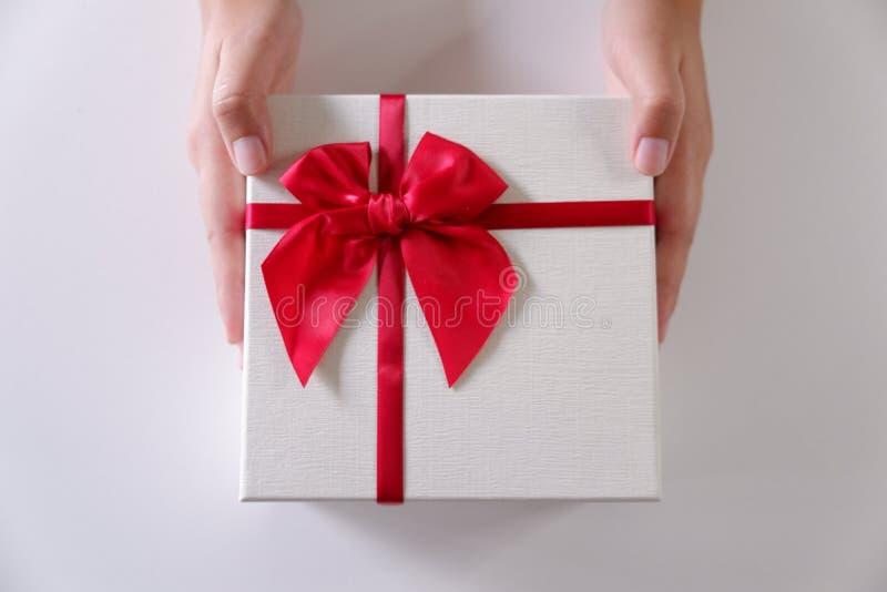 Mani delle donne del primo piano che inviano il contenitore di regalo bianco con il nastro rosso su fondo bianco immagini stock