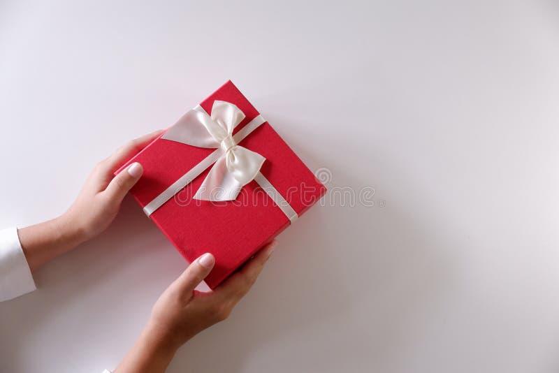 Mani delle donne del primo piano che inviano il contenitore di regalo rosso con il nastro bianco su fondo bianco fotografia stock
