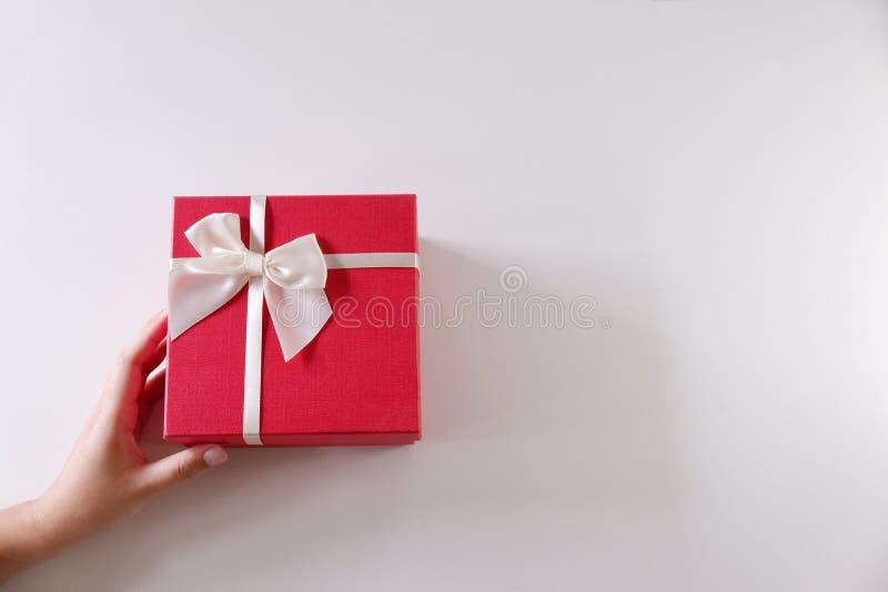 Mani delle donne del primo piano che inviano il contenitore di regalo rosso con il nastro bianco su fondo bianco fotografie stock libere da diritti