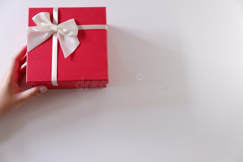 Mani delle donne del primo piano che inviano il contenitore di regalo rosso con il nastro bianco su fondo bianco immagine stock libera da diritti