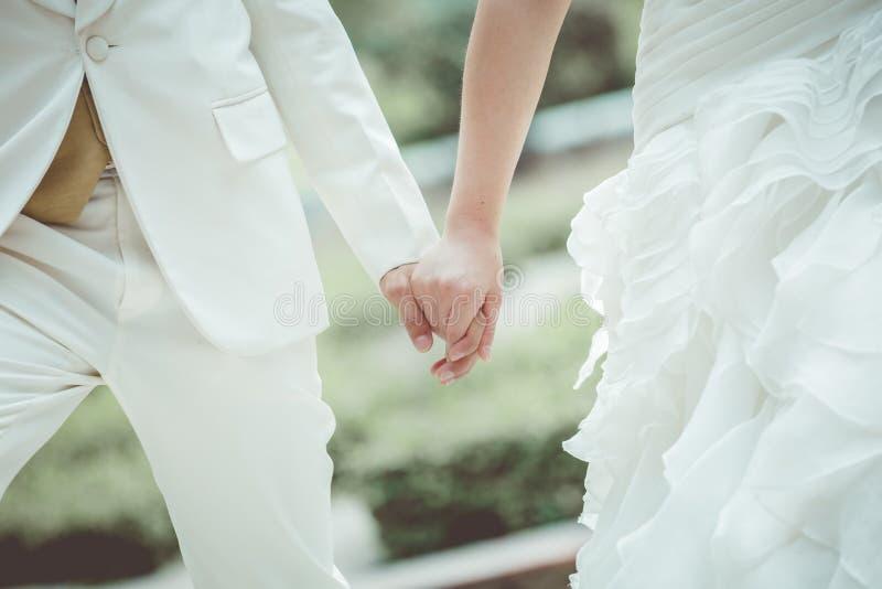 Mani delle persone appena sposate che hanno preso un simbolo di amore immagini stock