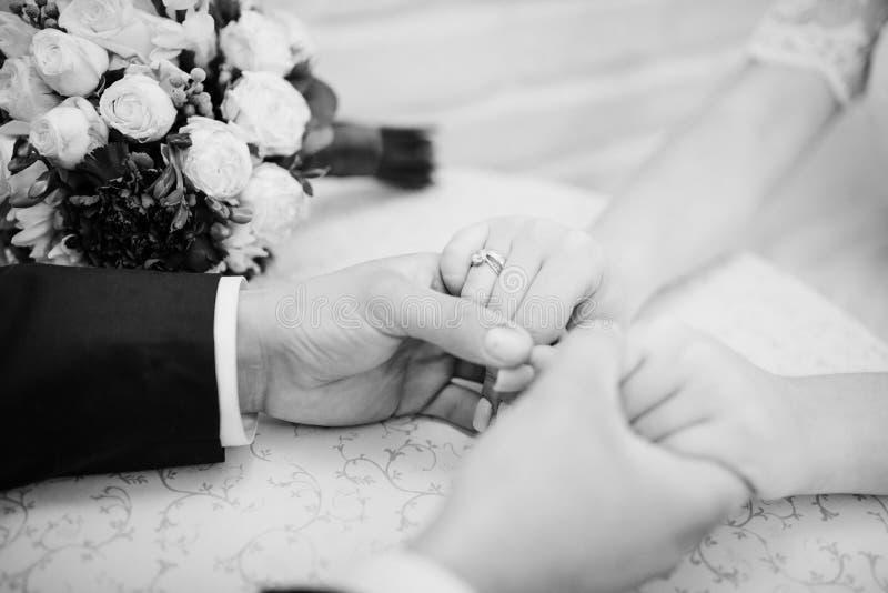 Mani delle spose alle mani dello sposo contro il mazzo di nozze Annerisca fotografia stock