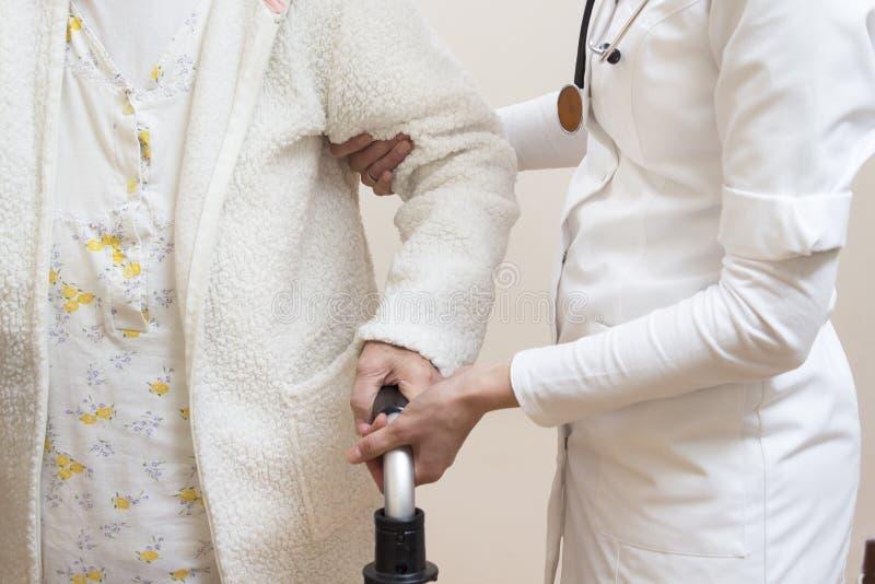 Mani di aiuto e dell'atto del legare di un medico una donna anziana e una mano della donna anziana che tengono un camminatore di  immagini stock