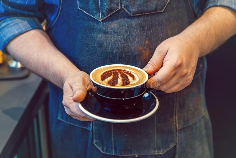 Mani di barista che tengono il cappuccino nero della tazza di caffè con il segno di logo della squadra di pallacanestro di Toront fotografia stock libera da diritti
