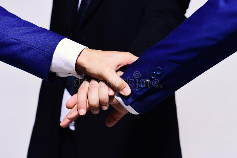 Mani di Businessmens che indossano usura convenzionale su fondo grigio fotografia stock libera da diritti