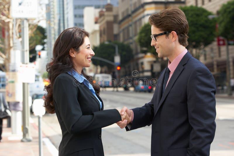 Mani di And Businesswoman Shaking dell'uomo d'affari in via fotografia stock