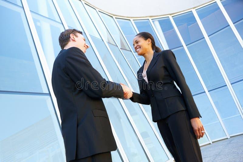 Mani di And Businesswomen Shaking dell'uomo d'affari fuori dell'ufficio immagini stock