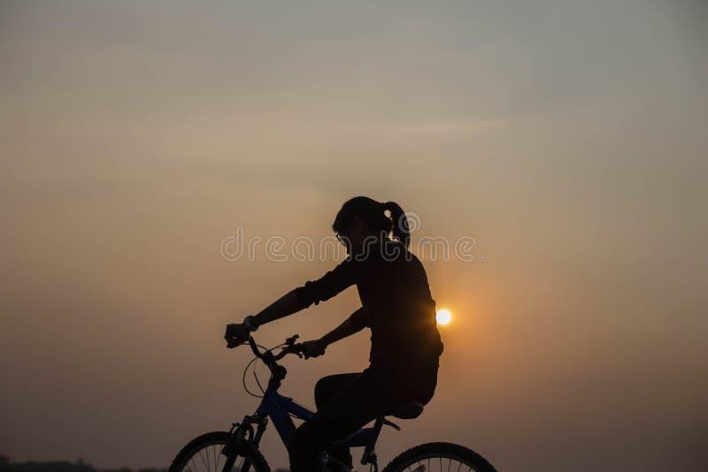 Mani di ciclismo della donna al tramonto fotografia stock libera da diritti