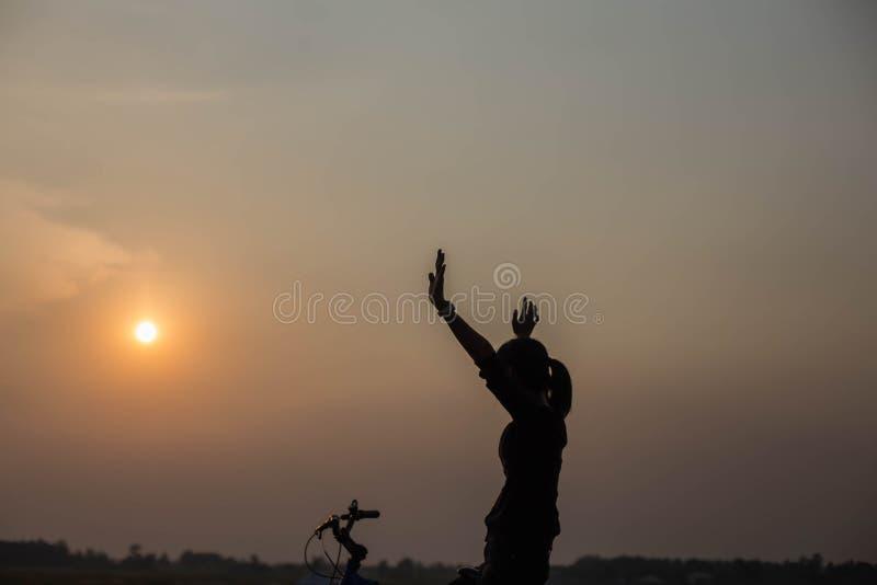 Mani di ciclismo della donna al tramonto fotografie stock libere da diritti