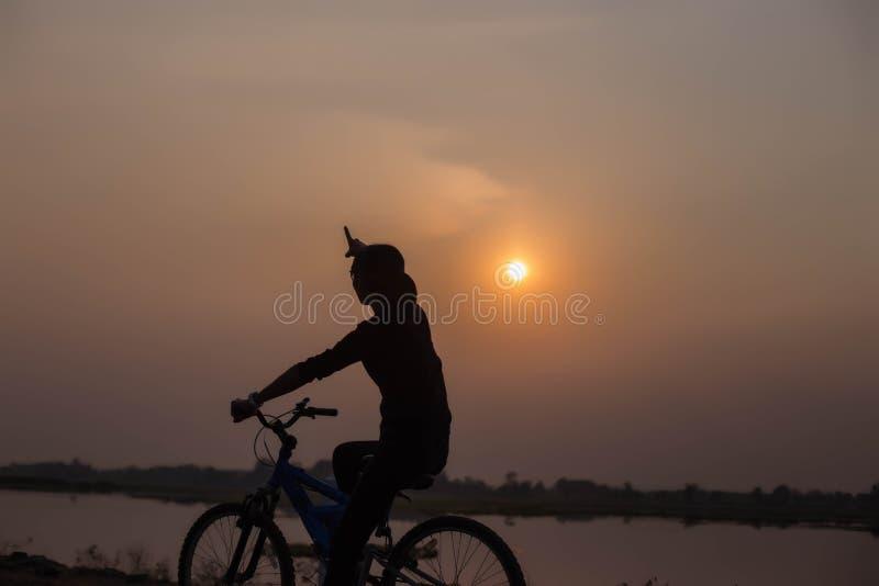 Mani di ciclismo della donna al tramonto immagini stock