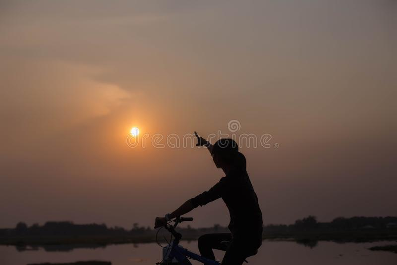 Mani di ciclismo della donna al tramonto immagine stock libera da diritti