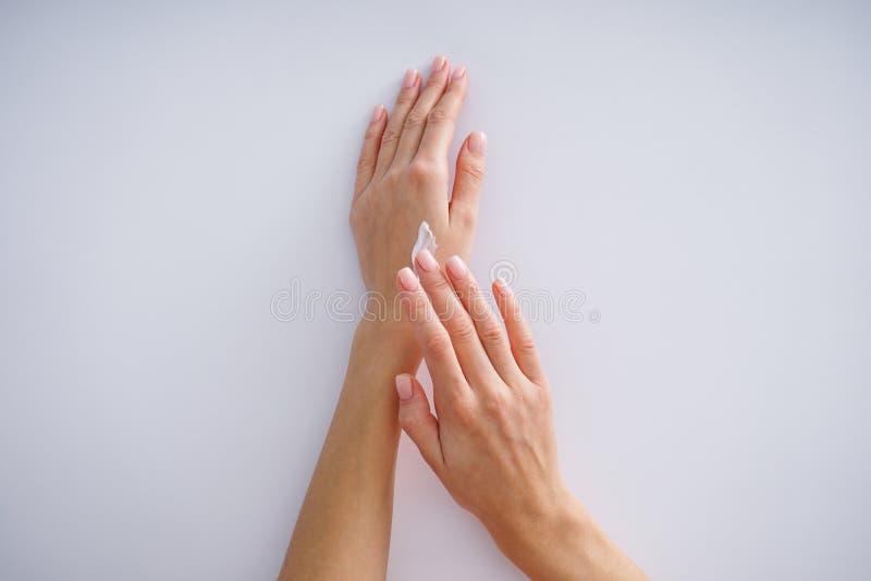 Mani di crema e una bella manicure su fondo grigio Trattamento della Spa fotografie stock libere da diritti