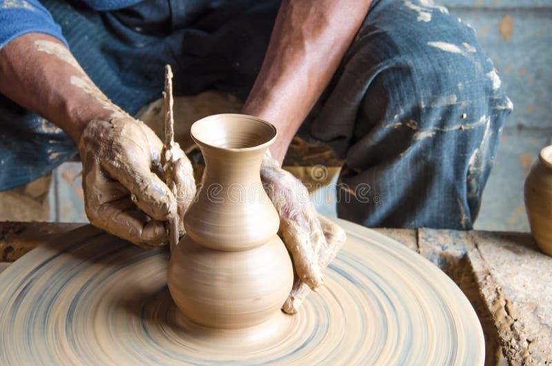Mani di fabbricazione del vaso di argilla sulla ruota delle terraglie, fuoco scelto, primo piano fotografia stock libera da diritti