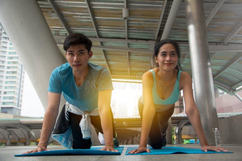 Mani di forza della donna e dell'uomo spingendo verso l'alto esercizio immagine stock