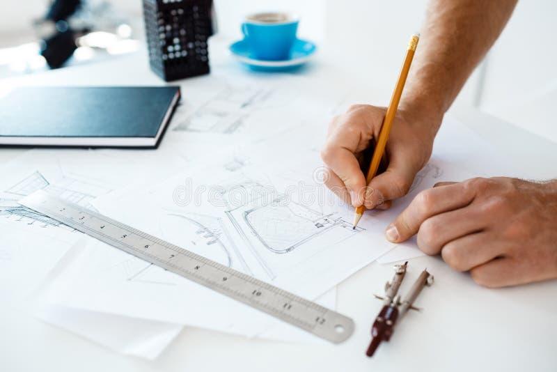 Mani di giovane schizzo della matita e del disegno della tenuta dell'uomo d'affari alla tavola Fondo moderno bianco dell'interno  fotografia stock libera da diritti
