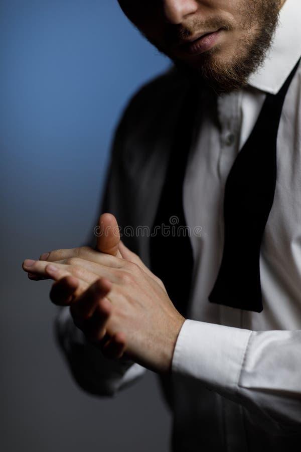 Mani di giovane uomo barbuto in camicia e cravatta a farfalla sciolta fotografie stock libere da diritti