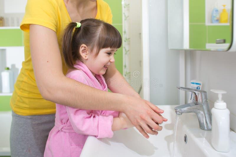 Mani di lavaggio del bambino con la mamma immagini stock libere da diritti